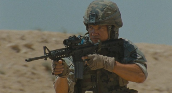 SFC James (Jeremy Renner) with his M4 during the scene where Bravo Company EOD confronts a group of British private military contractors in the desert. Note that James is wearing a woodland camouflage helmet cover and Interceptor vest, as opposed to the current-issue UCP pattern.